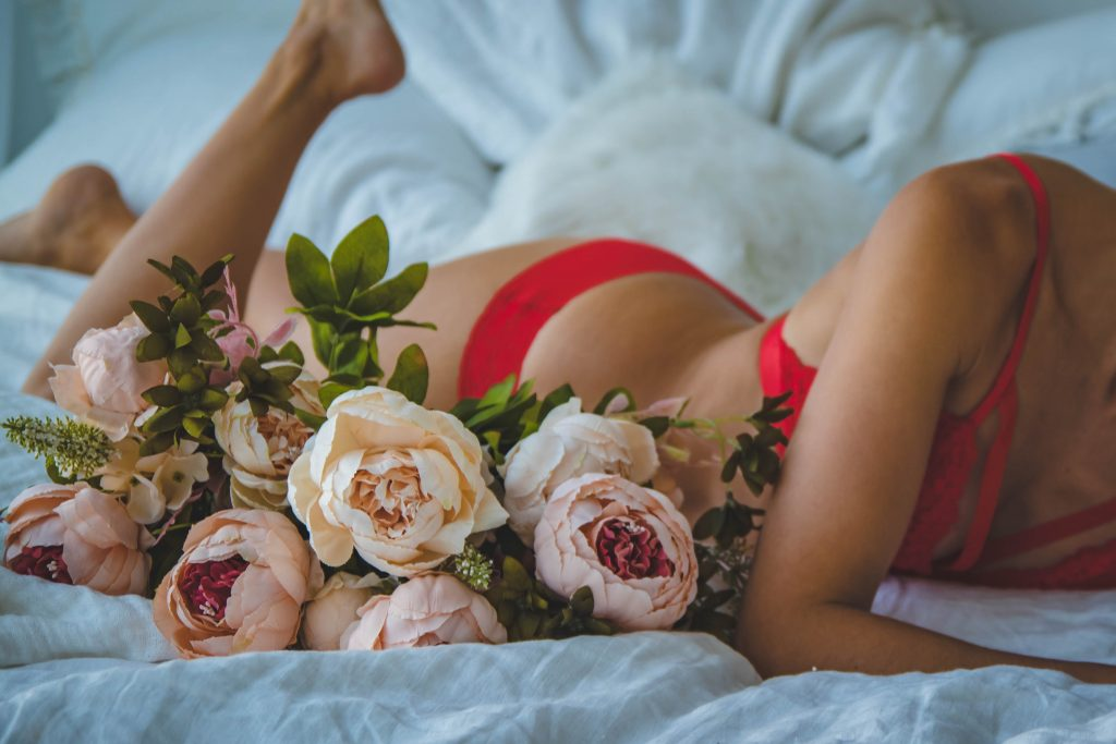 sexy girl on bed with flowers as a treat and a  present